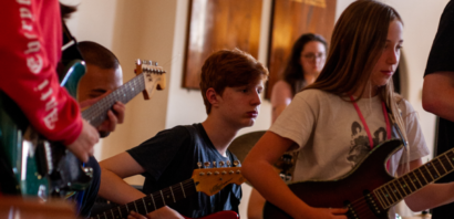 A group of young musicians playing electric guitar